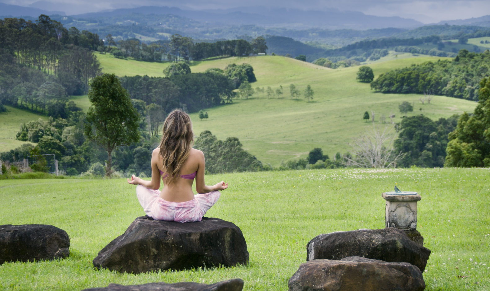 woman-meditating-rock-green-nature-landscape-drifting-away-gaia-retreat-spa-australia