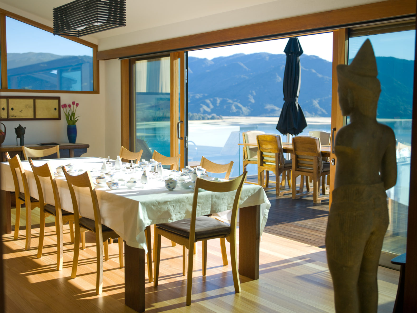 dining-room-ocean-hill-view-open-windows-buddha-split-apple-retreat-new-zealand