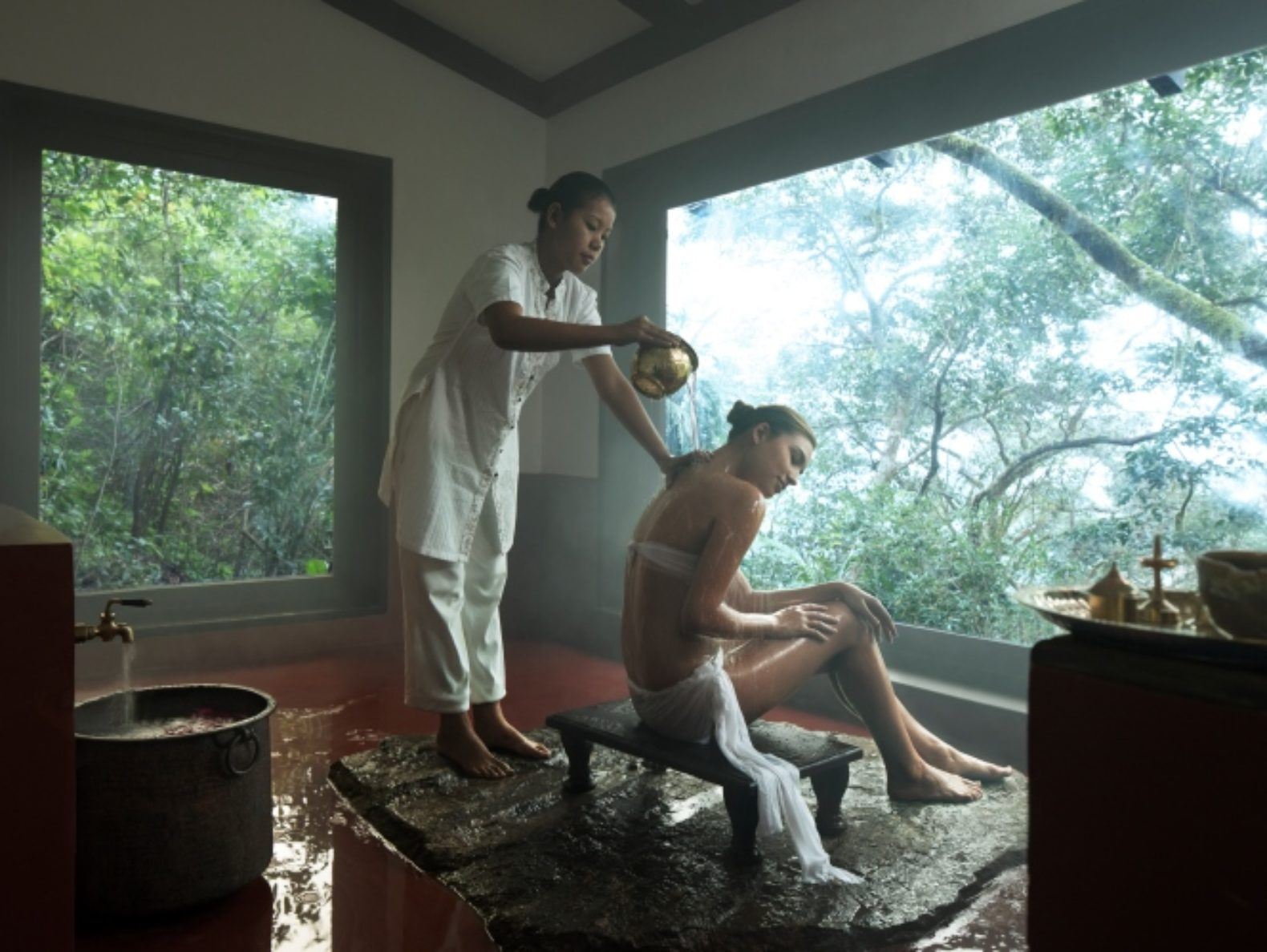 A SEARCH PICTURE_TVC_GuddaBath_Ayurvedic cleansing ritual woman bath_indoor thermal spa with panoramic view_Vivanta by Taj - Madikeri, Coorg, India
