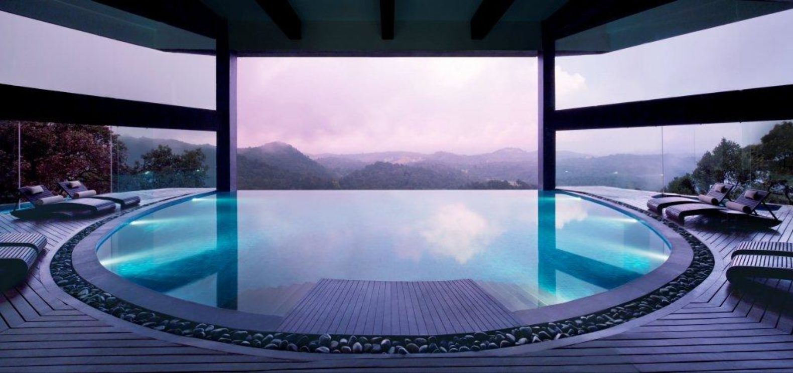 Indoor pool with beautiful view over mountain forest sunset and clouds Vivanta By Taj - Madikeri, Coorg India