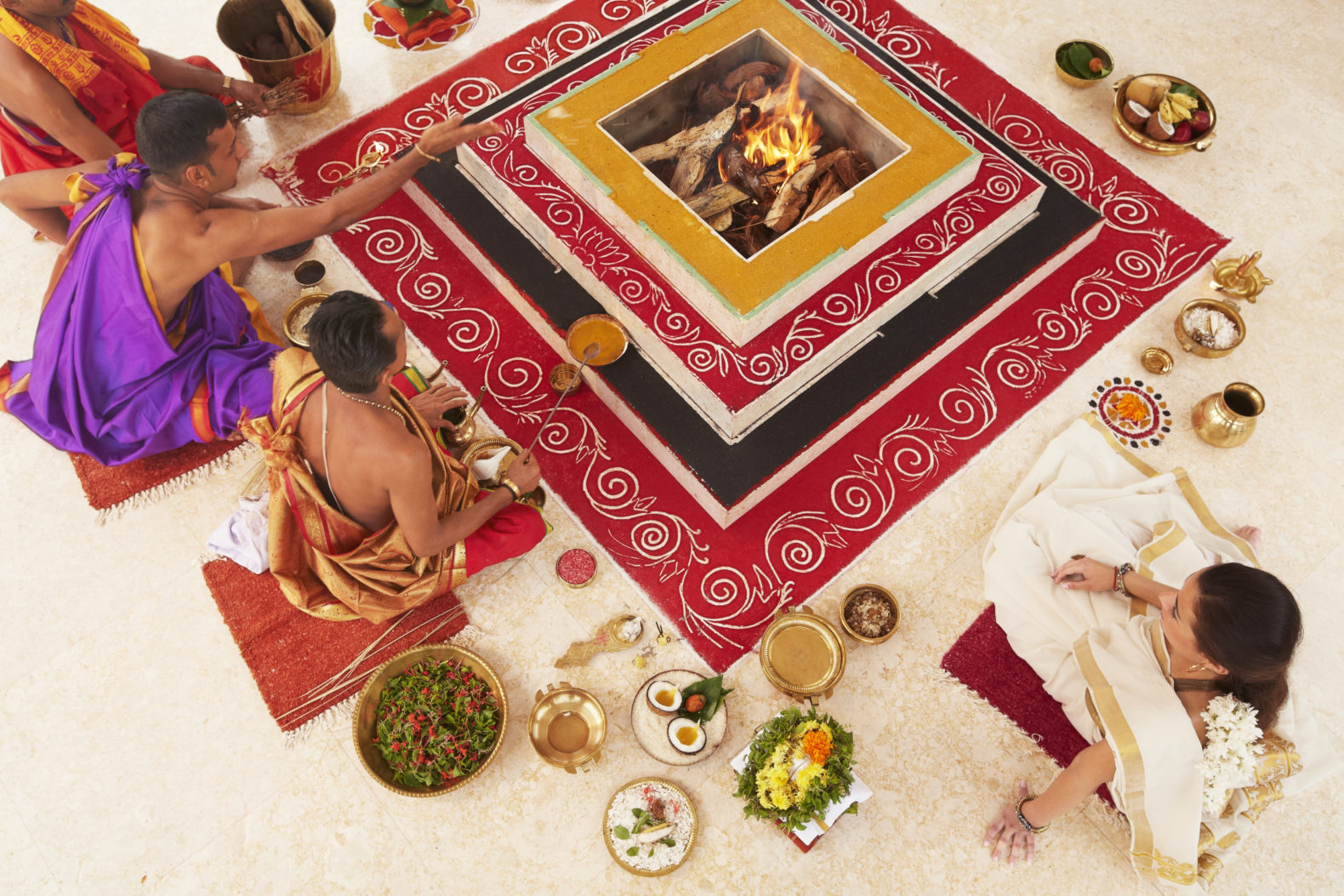 Traditional Food Ritual sitting on the floor around fire place with healthy bowls_Vivanta By Taj-Bekal India