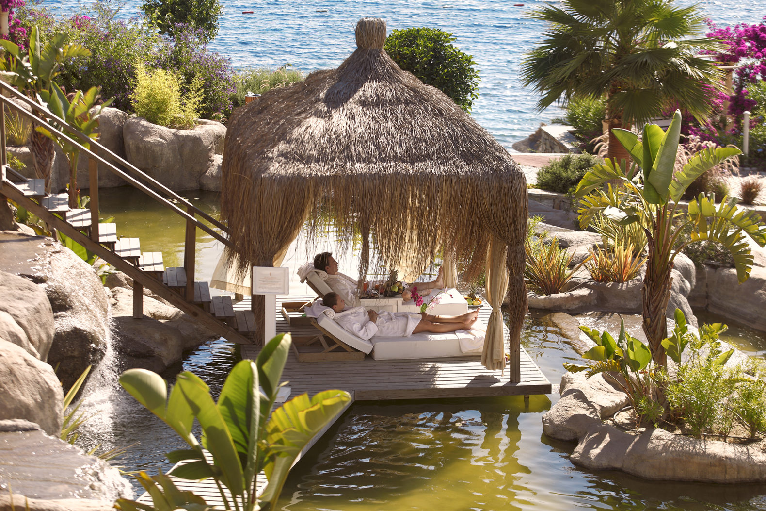 couple-relaxing-private-island-wood-sunbed-pool-sianji-wellbeing-resort-turkey