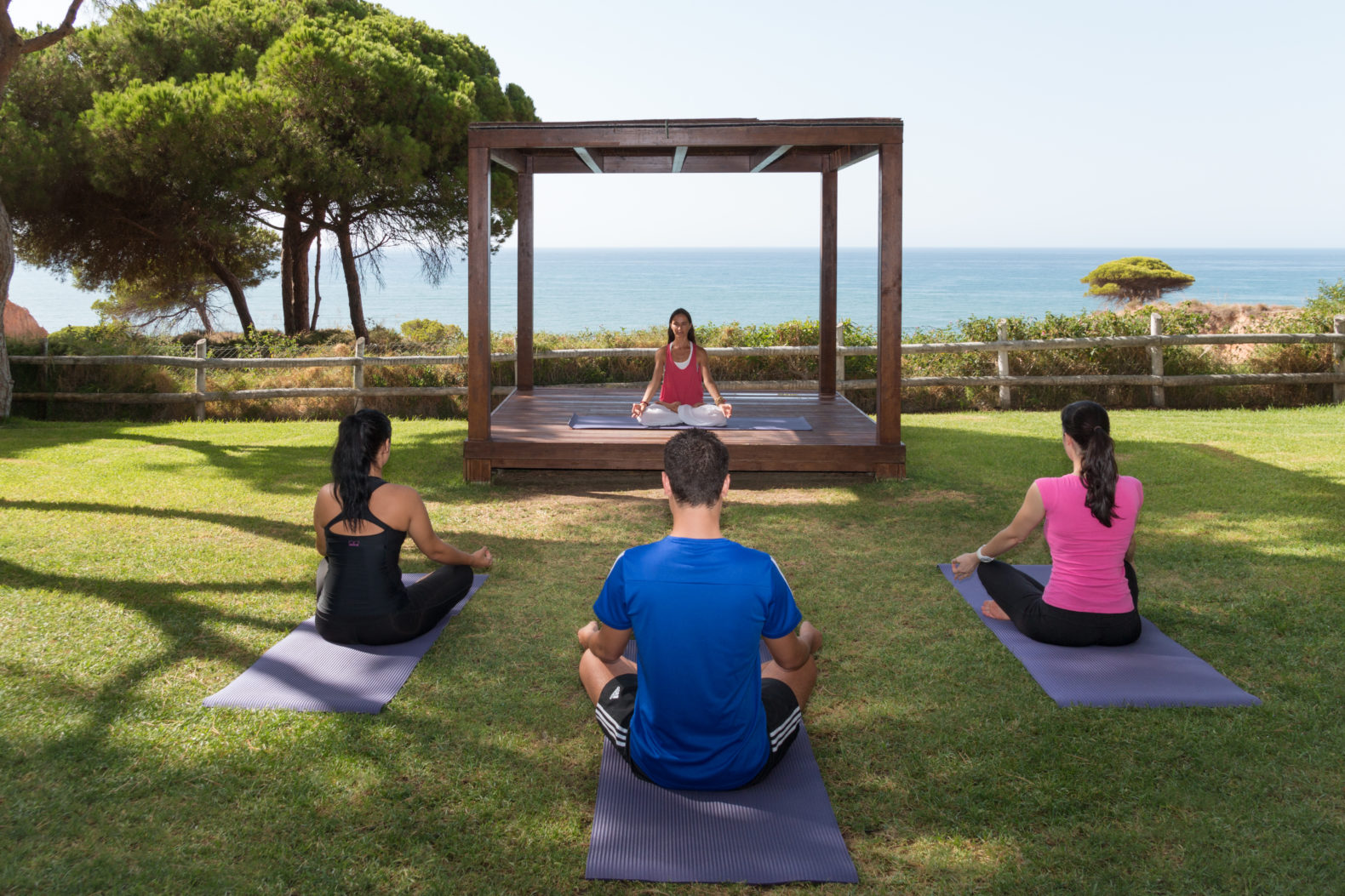 outdoor-yoga-group-session-grass-trees-ocean-view-pine-cliff-resort-algarve-portugal