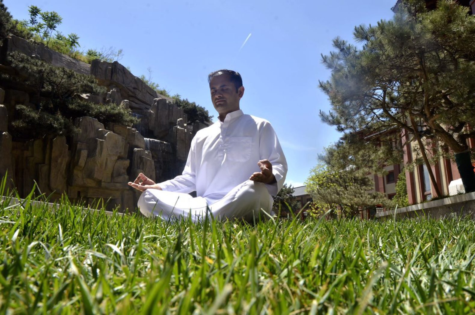 man-meditating-outside-grass-sky-grand-bay-beijing-china-healing-center