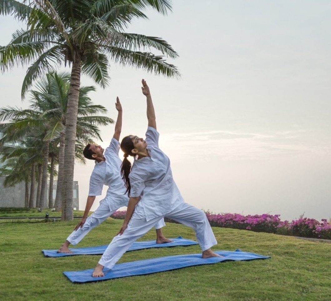 people-yoga-class-outside-grass-palmtrees-pema-health-healing-resort-india-hotel-copy